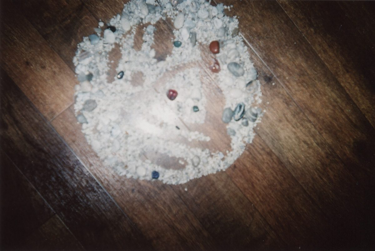 The image shows a piece of artwork by Jina Wallwork. It is a photograph of a daily meditation created using stones. Stylistically this piece of artwork has links with land art and earthworks.